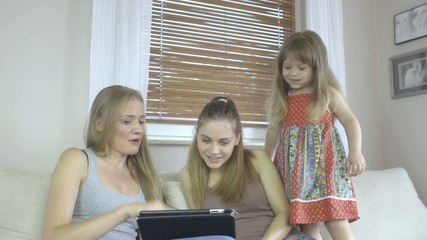 Two women and little girl with tablet computer relaxing at home