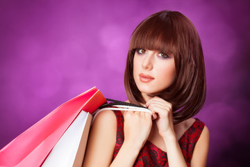 Brunette girl with shopping bags on violet background.