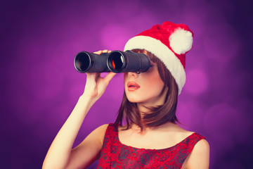 Brunette girl with binocular and hat on violet background.