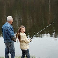 Grandfather and granddaughter are fishing