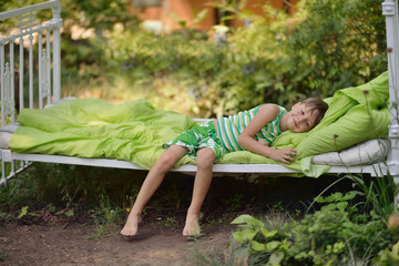 Outdoors in the green stands the white bed with a little cute bo