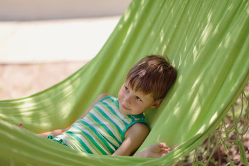 in a summer park little boy in a green shirt is in a hammock