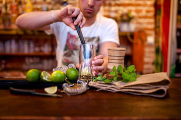 bartender preparing mojito cocktail drink, with limes, ice