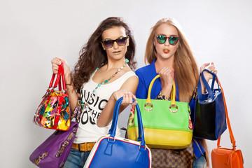 Две модные девушки и много разных сумок в руках