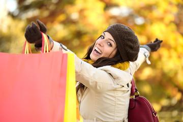 Blissful woman shopping and having fun in autumn