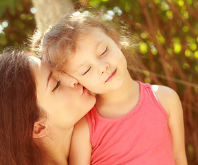 Enjoyment. Mother kissing happy kid with closed eyes