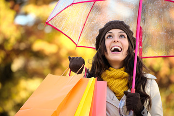 Woman holding shopping bags and umbrella in autumn