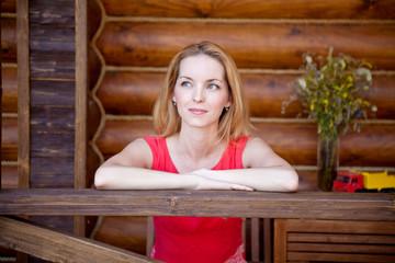 Красивая молодая девшка сидит возле деревянного домика