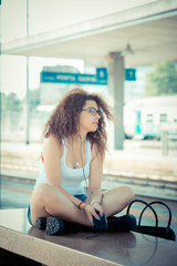 young beautiful long curly hair hipster woman listening music