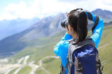 hiking woman taking photo at mountain peak in tibet,china