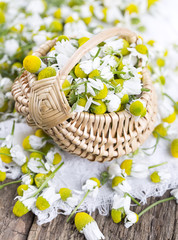 chamomile flowers in basket on wooden surface