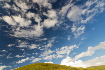 Green hill on blue sky clouds background