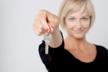 Happy smiling woman showing a key