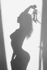 Beautiful naked woman silhouette, with sandals in hands