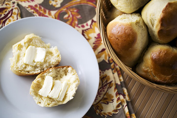 dinner rolls in basket and on white plate with butter