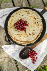 Pancakes with red currants. Near wooden spoon