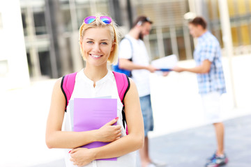 Young student standing and smiling in the campus