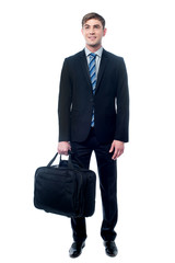 Businessman in black suit posing with bag