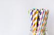 Leinwandbild Motiv Colorful Paper Straws in Mason Jar on White Background