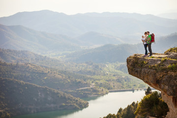 Young couple with toddler boy in sling standing on cliff