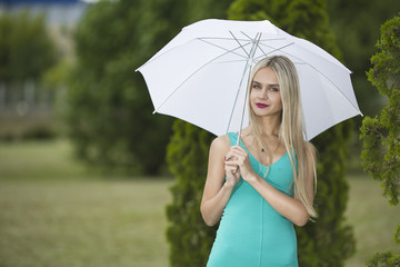 Beautiful young girl with an umbrella in park