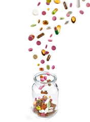 various medical pills falling into glass jar