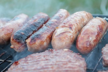 sausages and burgers cooking on barbecue