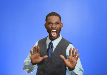 Angry executive gesturing with hands to stop, blue background
