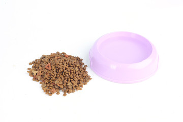 Dry cat food out of a purple pink bowl with water on white