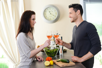 happy young couple cheering with a glass of wine in kitchen