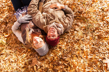 young couple lying on autumn leaves