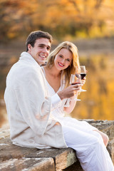 couple wrapped in blanket and enjoying wine at sunset