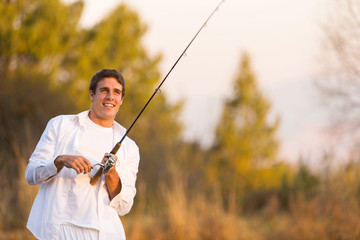young man catching a fish with rod