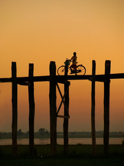 Silhouetted person on with a bike on U Bein Bridge at sunset, Am