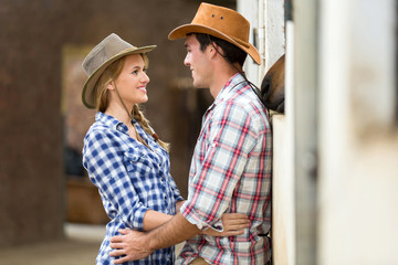 loving young couple inside stables