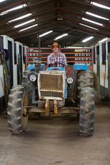 cowboy driving tractor inside stables
