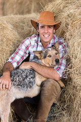 cowboy with his dog sitting on hay