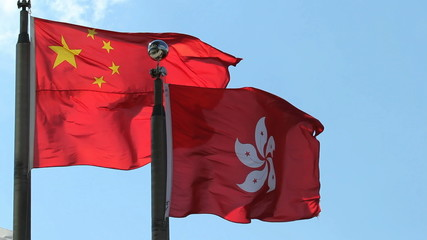 Hong Kong and China Flags flying against a clear blue sky