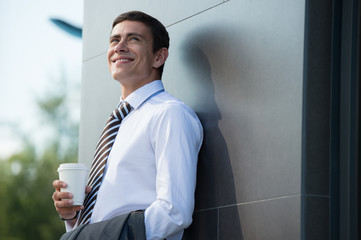 Businessman drinking coffee outdoors