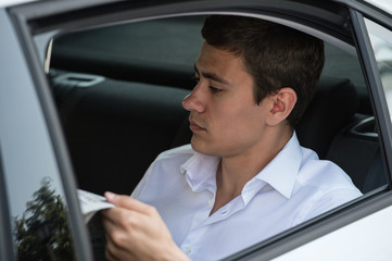 Businessman car reading newspaper