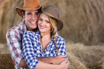 young farming couple hugging in barn