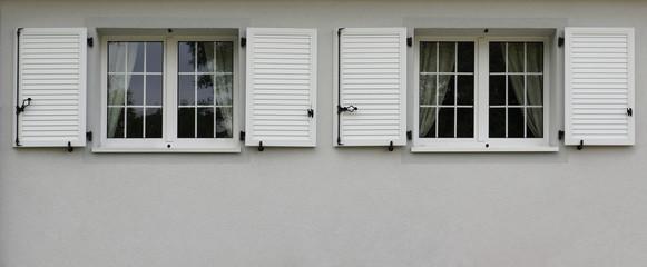 Zwei moderne Fenster mit Klappläden in grauer Fassade