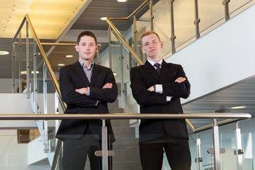 Two businessmen standing with arms crossed