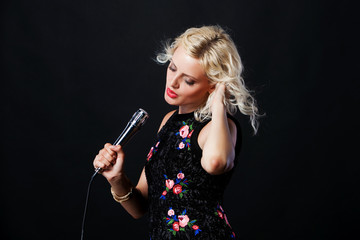 Beautiful young singing woman with microphone. Singer. Karaoke