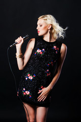 Beautiful blonde singing woman with microphone. Singer. Karaoke