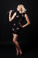 Full-length portrait of beautiful singing woman with microphone
