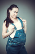 Pregnant beautiful girl in denim overall.  Pregnant woman posing