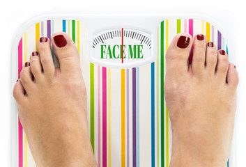 "Feet on bathroom scale with words ""Face me"" on dial"