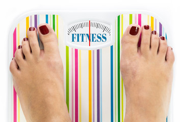 """Feet on bathroom scale with word """"Fitness"""" on dial"""