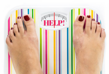 """Feet on bathroom scale with word """"Help"""" on dial"""